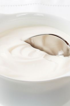 A bowl of Greek yoghurt with a spoon, white on white.