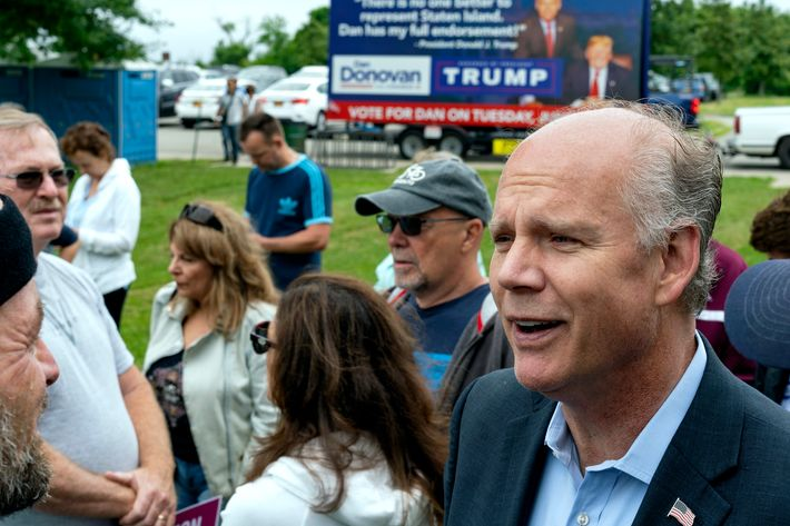 Incumbent Rep. Dan Donovan speaks to supporters and participants as he attends a property tax protest rally in the Staten Island on Saturday, June 23, 2018. In the background is a campaign billboard advertising President Trump's endorsement on Donovan.