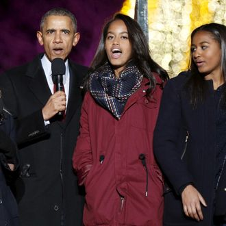 U.S. President Obama sings carols along with singer Blacc, actress Witherspoon and his daughters during the National Christmas Tree Lighting and Pageant of Peace ceremony in Washington