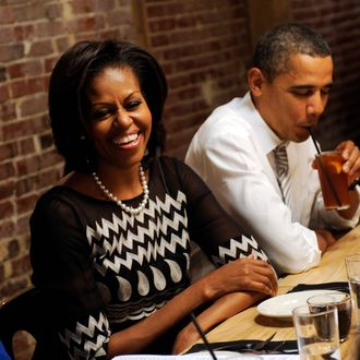 WASHINGTONG, DC - MARCH 8: U.S. President Barack Obama (R) and First Lady Michelle Obama have dinner with campaign contestant winners on March 8, 2012 at the Boundary Road in Washington, DC. The contestants were winners of a Democratic campaign contest to have dinner with the Obama's, and is the third such dinner event. (Photo by Leslie E. Kossoff-Pool/Getty Images)