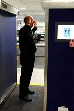 A security official (R) prepares to scan his colleague posing inside a RapiScan full-body scanner being trialled by Manchester Airport, during a photocall at the airport, in Manchester, northern England January 7, 2010.  The radiation risk from full-body scanners used to improve airport security is low and unlikely to raise an individual's risk of cancer, U.S. experts said on yesterday.  Airports in Britain, the Netherlands and Canada have said they plan to use full-body scanners to foil future terror attempts like the Christmas Day attempt to blow up a Detroit-bound flight.  The United States has tested 40 whole-body scanners as part of a pilot program started after the Sept. 11 attacks, and this past October ordered 150 more.