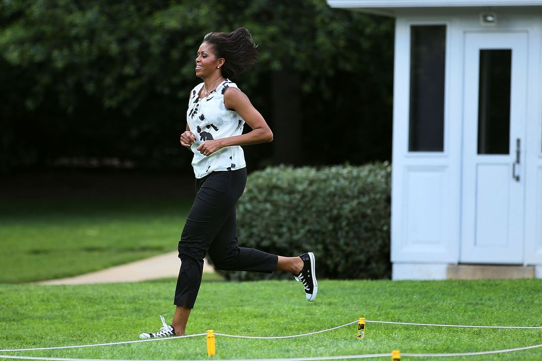 First lady Michelle Obama runs while working out with local students on the South Lawn of the White House on May 25, 2010 in Washington, DC. The first lady kicked off a series of South Lawn summer fitness activities for kids.