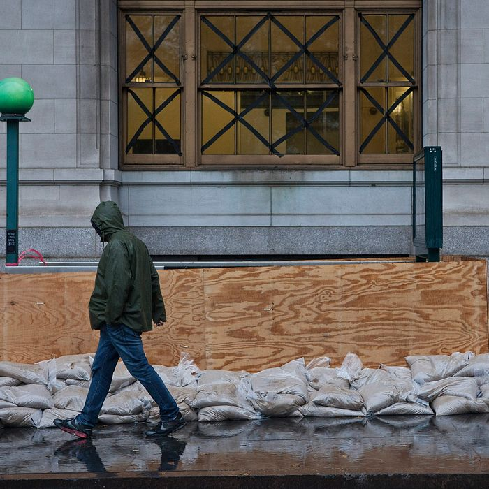 NEW YORK, NY - OCTOBER 29: A man walks past a barricaded subway entrance near Battery Park during the arrival of Hurricane Sandy on October 29, 2012 in New York City. The core of Sandy's force is supposed to hit the New York area Monday night. (Photo by Andrew Burton/Getty Images)