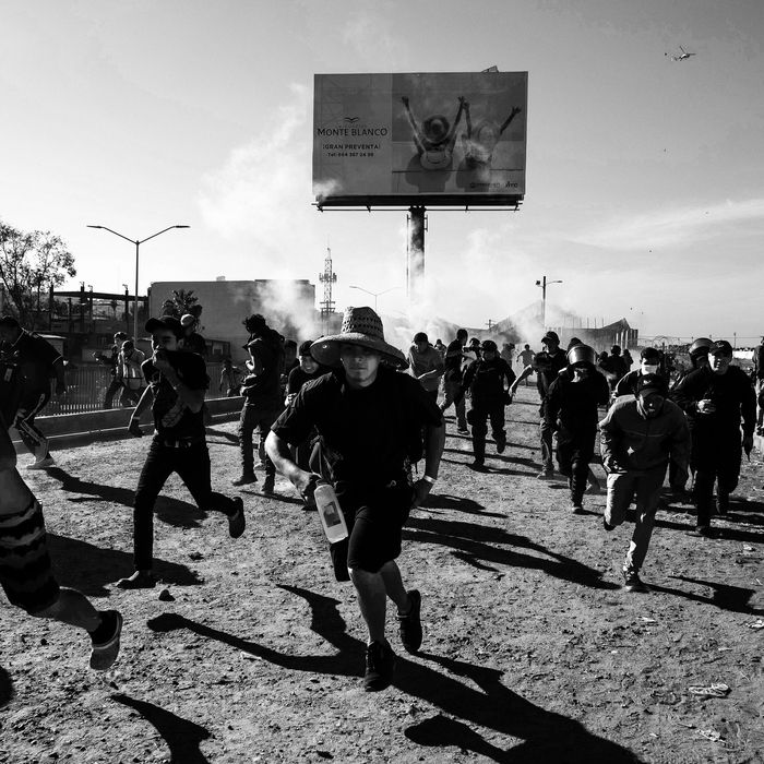 Asylum-seekers running from tear gas.