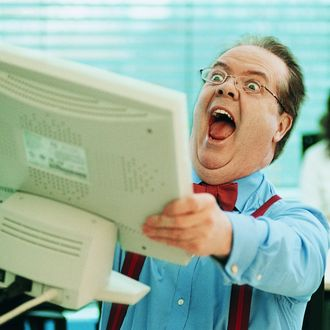 Surprised Businessman Holding a Computer Monitor in the Office --- Image by ? 13/Flying Colours Ltd/Ocean/Corbis