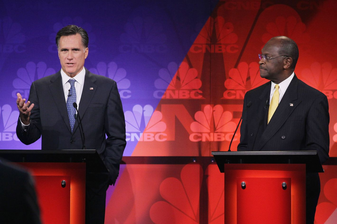 ROCHESTER, MI - NOVEMBER 09:  Former CEO of Godfather's Pizza Herman Cain (R) looks on as former Massachusetts Gov. Mitt Romney speaks during a debate hosted by CNBC and the Michigan Republican Party at Oakland University on November 9, 2011 in Rochester, Michigan. The debate is the first meeting of the eight GOP presidential hopefuls since allegations of sexual impropriety have surfaced against front-runner Herman Cain.   (Photo by Scott Olson/Getty Images)