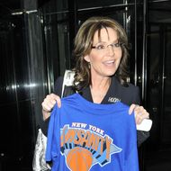 "PALINSANITY - Sarah Palin poses with a ""Linsanity"" shirt, promoting the hype around Asian-America NY Knicks player Jeremy Lin. Sarah was all smiles and even signed a few autographs as she made her way to her hotel in New York City wearing a jacket lapel that said ""Hooah"". Photograph:  (Newscom TagID: pacificphotos687886) [Photo via Newscom]"
