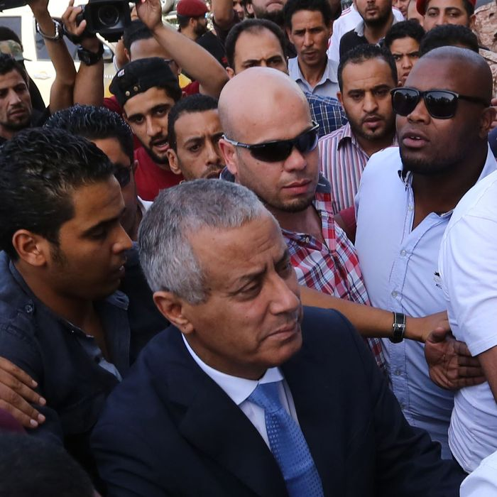 Libyan Prime Minister Ali Zeidan (C) arrives at the government headquarters in Tripoli on October 10, 2013 shortly after he was freed from the captivity of militiamen who had held him for several hours. Gunmen seized Zeidan from a hotel, where he resides, in the Libyan capital and held him for several hours before he was freed, in the latest sign of Libya's lawlessness since Moamer Kadhafi was toppled in 2011.
