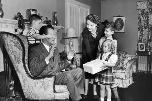 circa 1955:  A young boy covers his father's eyes with his hands as his two siblings and mother hold out a surprise gift. The father sits in an armchair near a fireplace in a living room.