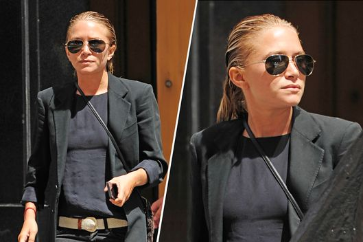 Mary-Kate Olsen, holding her iPhone, wears an all black outfit on a nice summer day while exiting an office building in Tribeca in New York City.