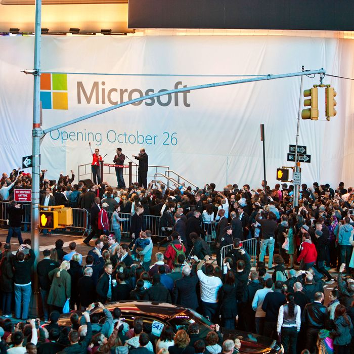 Kevin Turner, chief operating officer of Microsoft Corp., stage right, Panos Panay, general manager of Microsoft Surface, center, and Melinda George, Times Square store manager, attend the Microsoft Corp. store grand opening in New York, U.S., on Thursday, Oct. 25, 2012. Microsoft Corp. introduced the biggest overhaul of its flagship Windows software in two decades, reflecting the rising stakes in its competition with Apple Inc. and Google Inc. for the loyalty of customers who are shunning personal computers and flocking to mobile devices.