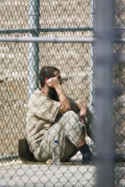 A detainee sits inside an outdoor recreation arear at Camp V, a maximum security part of Camp Delta 05 December 2006 at the US Naval Base in Guantanamo, Cuba. Approximately 445 enemy combatants from al Qaeda and the Taliban are in various security levels of lock-up in Camp Delta here by a US Joint Task Force.