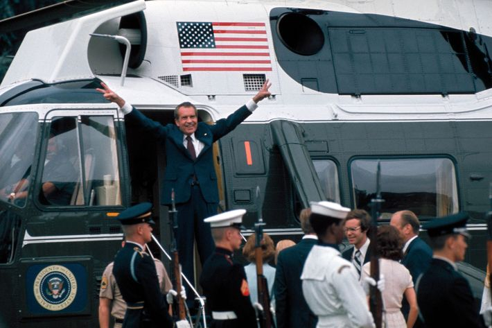 Pres. Richard Nixon raising hands w. trademark V signs in doorway of helicopter after leaving White House following his resignation over the Watergate scandal, 9th August 1974.