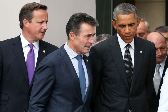 US President Barack Obama (R), NATO Secretary General Anders Fogh Rasmussen (C) and British Prime Minister David Cameron (L) arrive for the family photo at the start of the NATO 2014 summit in Newport, South Wales, on September 4, 2014. The NATO summit billed as the most important since the Cold War got underway Thursday with calls to stand up to Russia over Ukraine and confront Islamic State extremists.