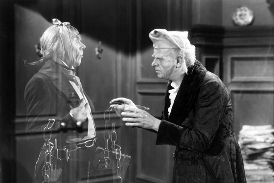 "ca. 1938 --- Original caption: Reginald Owen, playing Scrooge, speaks with his dead business partner Marley, played by Leo G. Carroll, during the 1938 MGM production of ""A Christmas Carol.""  Undated movie still. --- Image by © Bettmann/CORBIS"
