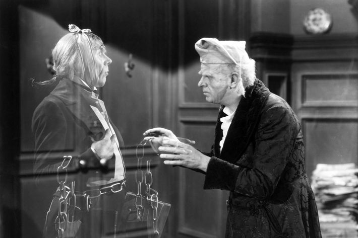 "Reginald Owen, playing Scrooge, speaks with his dead business partner Marley, played by Leo G. Carroll, during the 1938 MGM production of ""A Christmas Carol."""
