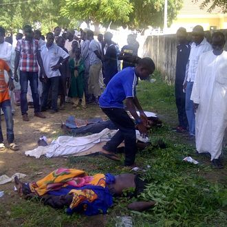 EDS NOTE GRAPHIC CONTENT : In this image taken with a mobile phone, rescue workers and family members gather to identify the shrouded bodies of students killed following an attack by Islamist extremist on an agricultural college in Gujba, Nigeria, Sunday, Sept. 29, 2013, Suspected Islamic extremists attacked the Yobe State College of Agriculture early Sunday, gunning down students as they slept in dormitories and torching classrooms, leaving some 50 students dead in the attack according to college Provost Molima Idi Mato. The attack is seen as part of an ongoing Islamic uprising in northeastern Nigeria prosecuted by Boko Haram militants in their declared quest to install an Islamic state. (AP Photo)