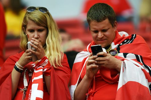 Swiss fans check the smartphones prior to a Group E football match between Switzerland and Ecuador at the Mane Garrincha National Stadium in Brasilia during the 2014 FIFA World Cup on June 15, 2014.
