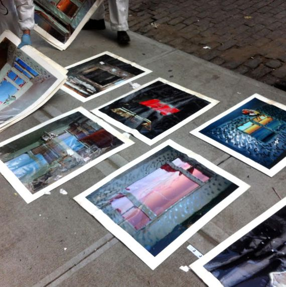Wrinkled photographs damaged by water laid on a sidewalk.