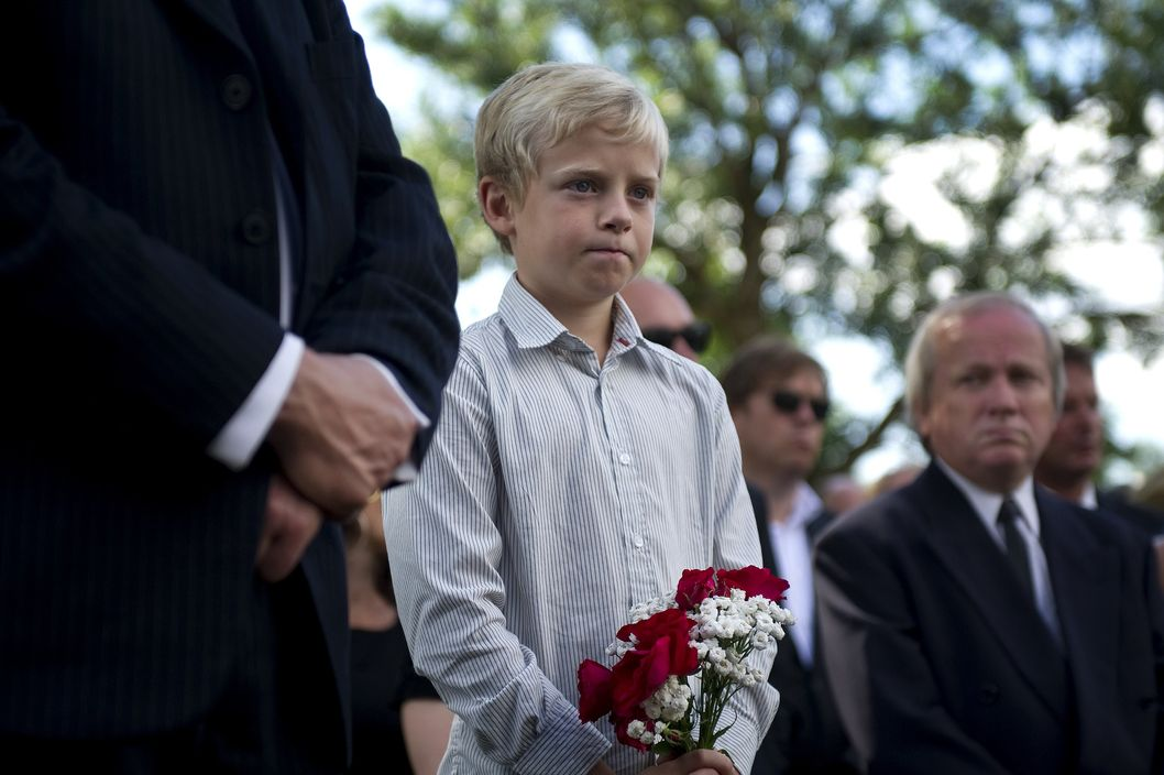 A boy holds a bunch of flowers as he watches the funeral procession of Bano Rashid (18), one of the victims of the massacre on the youth camp of the Norwegian Labour Party as they make their way to her gravesite at Nesodden Kirke south of the Norwegian capital Oslo on July 29, 2011. Norway was burying today the first victims of the twin attacks that killed 76 people exactly one week before, as police questioned the killer for a second time. Police said prosecutors had appointed two psychiatrists to assess the mental health of Anders Behring Breivik, 32, and determine if he is criminally responsible.Norway was burying Friday the first victims of the twin attacks that killed 76 people exactly one week before, as police questioned the killer for a second time.  AFP PHOTO / ODD ANDERSEN (Photo credit should read ODD ANDERSEN/AFP/Getty Images)