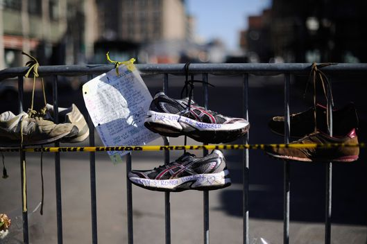 BOSTON, MA - APRIL 21:  Running shoes are placed at a makeshift memorial for victims near the finish line of the Boston Marathon bombings at the intersection of Newbury Street and Darthmouth Street two days after the second suspect was captured  on April 21, 2013 in Boston, Massachusetts. A manhunt for Dzhokhar A. Tsarnaev, 19, a suspect in the Boston Marathon bombing ended after he was apprehended on a boat parked on a residential property in Watertown, Massachusetts. His brother Tamerlan Tsarnaev, 26, the other suspect, was shot and killed after a car chase and shootout with police. The bombing, on April 15 at the finish line of the marathon, killed three people and wounded at least 170.  (Photo by Kevork Djansezian/Getty Images)