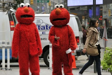 People, dressed as Elmo from the television show Sesame Street, wait to pose for pictures with tourists in through Times Square October 4, 2012. GOP Presidential nominee Mitt Romney mentioned Sesame Street in Wednesday night's debate when he vowed to cut funding to public broadcasting if elected. PBS's Sesame Street will be celebrating its 43rd birthday this year. AFP PHOTO/ TIMOTHY A. CLARY (Photo credit should read TIMOTHY A. CLARY/AFP/GettyImages)