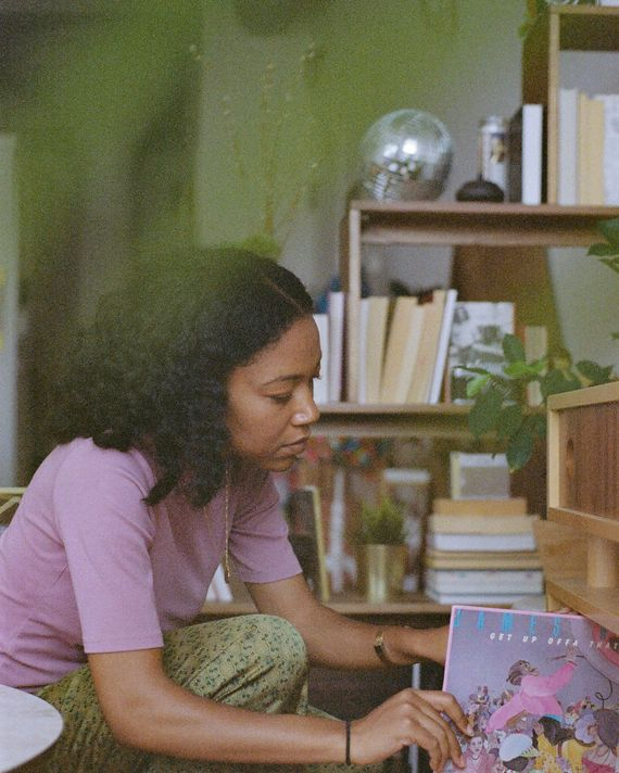 A woman pulling a record off of a shelf