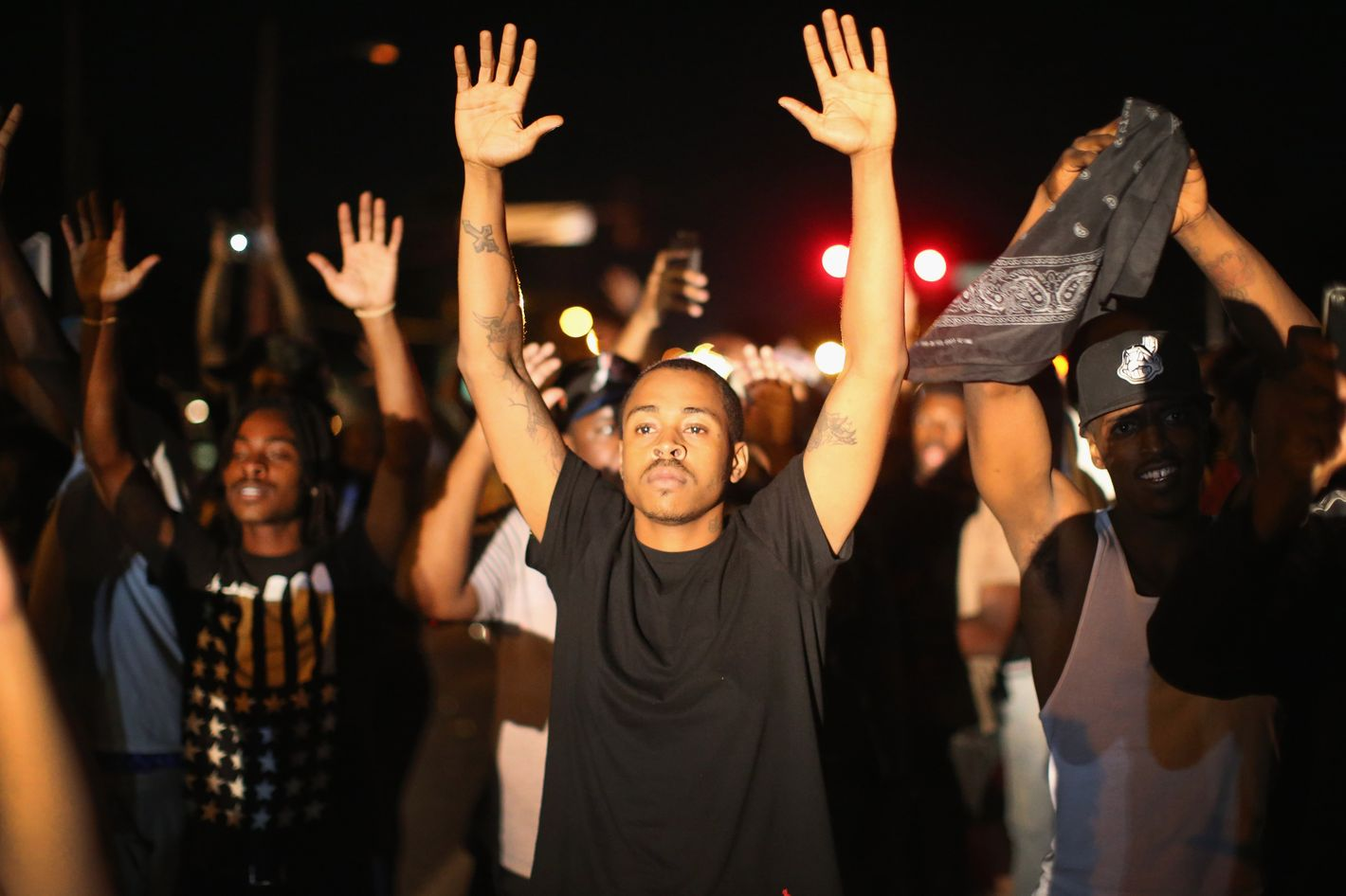 FERGUSON, MO - AUGUST 12:  Demonstrators protest the killing of teenager Michael Brown on August 12, 2014 in Ferguson, Missouri. Brown was shot and killed by a police officer on Saturday in the St. Louis suburb of Ferguson. Ferguson has experienced two days of violent protests since the killing but, tonight's protest was peaceful.  (Photo by Scott Olson/Getty Images)