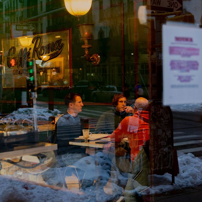 Several people sitting inside Caffe Roma as seen through the street window.