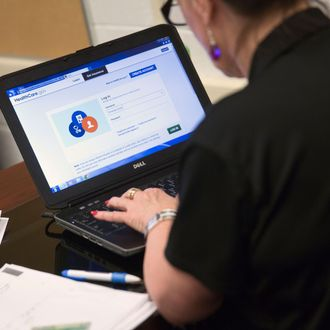 Marketplace guide Sharon Hamby works on the Healthcare.gov federal enrollment website as she helps a resident sign up for a health insurance plan under the Affordable Care Act at an enrollment event in Milford, Delaware, U.S., on Thursday, March 27, 2014. Six million Americans have signed up for private health plans under Obamacare, President Barack Obama said, a symbolic milestone for a government that has struggled to get the law off the ground. Photographer: Andrew Harrer/Bloomberg via Getty Images