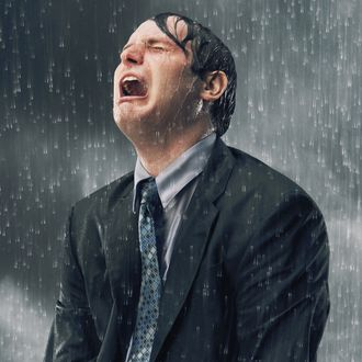 Businessman crying in rain