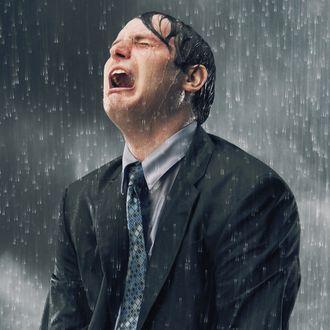 Businessman crying in rain