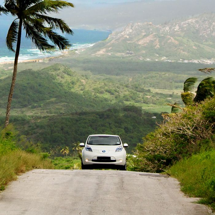 An electric vehicle drives through Cherry Tree Hill, Barbados.