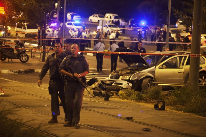 Israeli policemen stand guard at the scene after a car rammed a group of pedestrians near the light rail train station near Ammunition Hill October 22, 2014 in Jerusalem, Israel. A 3 month baby was killed and several people were wounded on Wednesday evening in a suspected terror attack near the light rail train station near Ammunition Hill in Jerusalem. According to eyewitnesses, a car drove up to the station and ran over passersby disembarking from the train.
