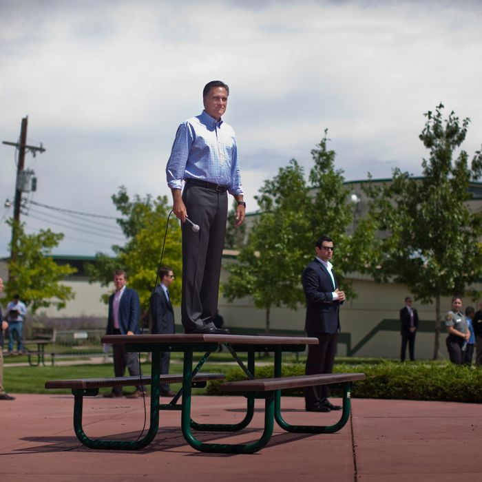 Surrounded by Secret Service, Republican Presidential candidate Mitt Romney hops on a picnic table to address a crowd gathering outside the Jefferson County Fairgrounds building in Golden, Colorado, on Thursday August 2, 2012.