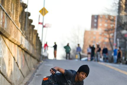Young male skateboarder on urban street.