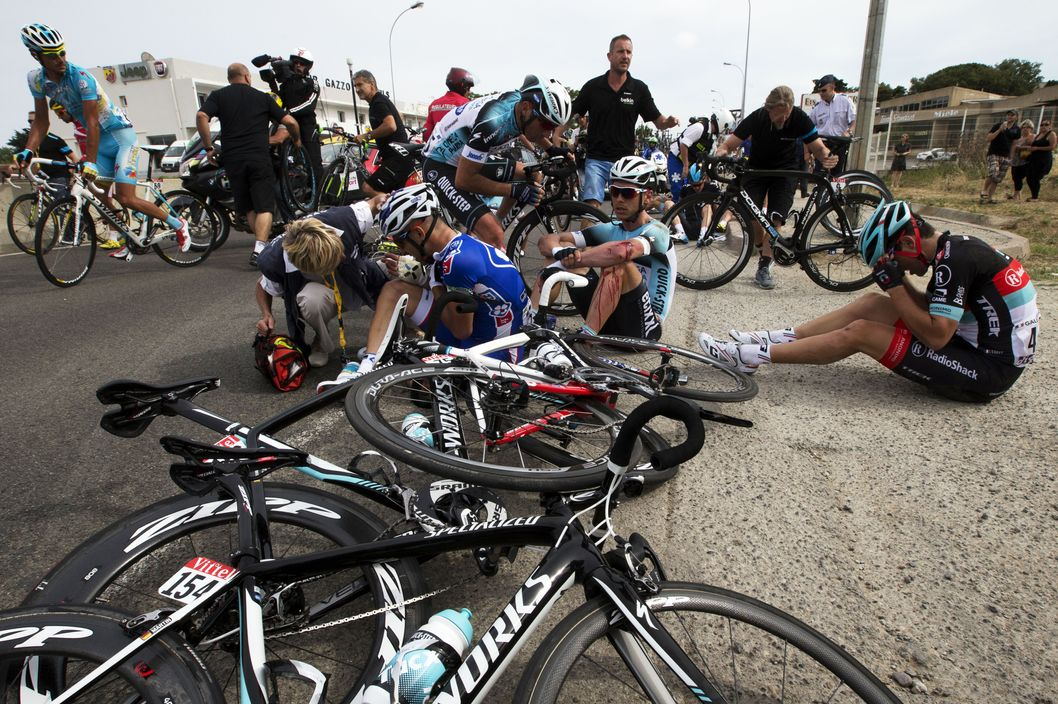 Brazil's Murilo Antoniobil Fischer (C-L), Germany's Tony Martin (C), and France's Tony Gallopin (R) sit on the ground after a fall during the 213 km first stage of the 100th edition of the Tour de France cycling race on June 29, 2013 between Porto-Vecchio and Bastia, on the French Mediterranean Island of Corsica.