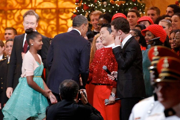 """WASHINGTON, DC - DECEMBER 9: (AFP OUT) U.S. President Barack Obama shakes hands with South Korean musician PSY (C), next to host Conan O'Brien (L) and performer Scotty McCreery (R) during the """"Christmas in Washington"""" concert at the National Building Museum on December 9, 2012 in Washington, D.C. The concert benefits the National Childrens Medical Center and is hosted by comedian Conan O'Brien. (Molly Riley-Pool/Getty Images)"""