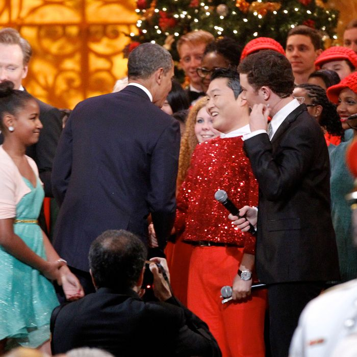 WASHINGTON, DC - DECEMBER 9: (AFP OUT) U.S. President Barack Obama shakes hands with South Korean musician PSY (C), next to host Conan O'Brien (L) and performer Scotty McCreery (R) during the