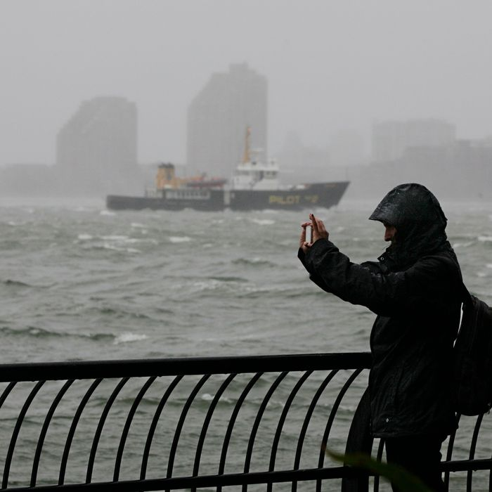 A woman uses her mobile phone to photograph New York Harbor at Battery Park, at the southern tip of Manhattan, Monday, Oct. 29, 2012. Defiant New Yorkers jogged, pushed strollers and took snapshots of churning New York Harbor on Monday, trying to salvage normal routines in a city with no trains, schools and an approaching mammoth storm.