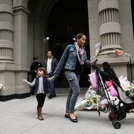 NEW YORK, NY - OCTOBER 26: People walk by flowers and messages that have been left in front of the building where two children were stabbed to death allegedly by their nanny in a family's Upper West Side apartment on October 26, 2012 in New York City. The New York Police department said that the children were discovered in a bathtub by their mother, Marina Krim. Their nanny, Yoselyn Ortega, 50, was lying unconscious nearby with apparent self-inflicted stab wounds. As the investigation continues no charges have been filed at this time. (Photo by Spencer Platt/Getty Images)