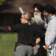 OAK CREEK, WI - AUGUST 05:  A police officer directs people near the Sikh Temple of Wisconsin where at least one gunman stormed the mass and opened fire August, 5, 2012 Oak Creek, Wisconsin. At least six people are reported to have been killed when a shooter, who was shot dead by a police officer, opened fire on congregants in the Milwaukee suburb.  (Photo by Scott Olson/Getty Images)