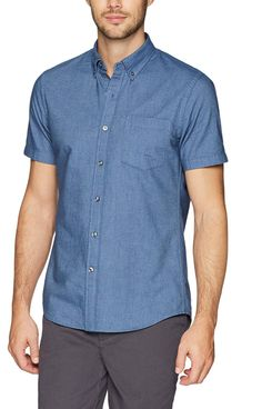 A male model wearing a a blue denim slim-fit short-sleeve Oxford button-down with a breast pocket and a collar from Goodthreads and a pair of grey trousers. The Strategist - A Bunch of Men's Button Downs (From $16) Are on Sale at Amazon.