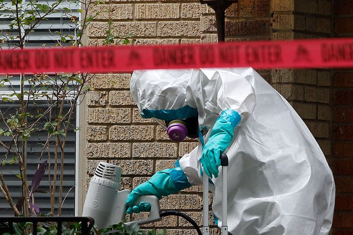 DALLAS, TX - OCTOBER 12:  A man dressed in protective hazmat clothing treats the front porch of an apartment where a second person diagnosed with the Ebola virus resides on October 12, 2014 in Dallas, Texas. A female nurse working at Texas Heath Presbyterian Hospital, the same facility that treated Thomas Eric Duncan, has tested positive for the virus. (Photo by Mike Stone/Getty Images)