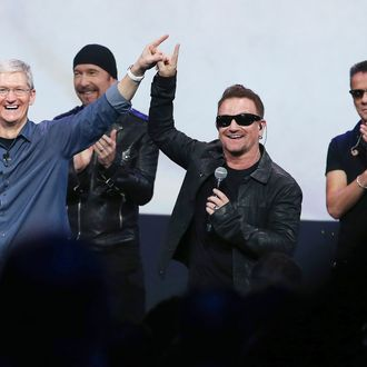 CUPERTINO, CA - SEPTEMBER 09: Apple CEO Tim Cook (L) greets the crowd with U2 singer Bono (2nd R) as The Edge (2nd L) and Larry Mullen Jr look on during an Apple special event at the Flint Center for the Performing Arts on September 9, 2014 in Cupertino, California. Apple unveiled the Apple Watch wearable tech and two new iPhones, the iPhone 6 and iPhone 6 Plus. (Photo by Justin Sullivan/Getty Images)