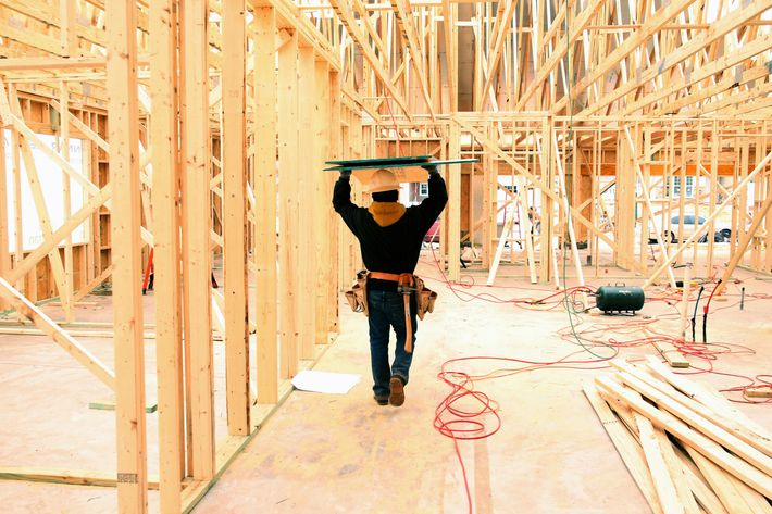 A contractor carries boards through a house under construction in Lancaster, South Carolina.