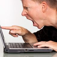 Angry man with laptop computer aa pointing