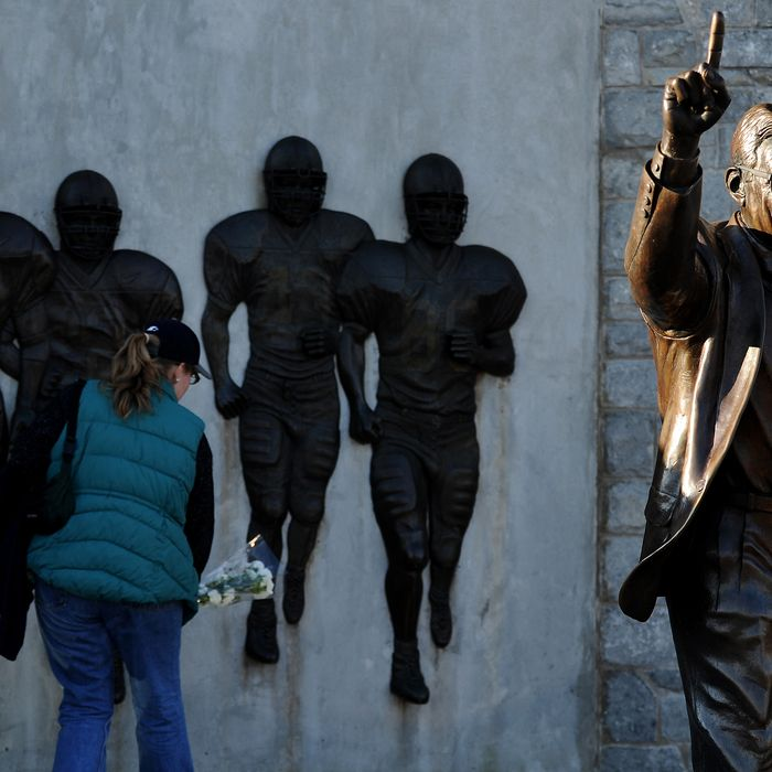 STATE COLLEGE, PA - NOVEMBER 12: A fan pays respect to a statue of former Penn State football coach Joe Paterno before the Penn State against Nebraska football game at Beaver Stadium on November 12, 2011 in State College, Pennsylvania. Head football coach Joe Paterno was fired amid allegations that former Penn State defensive coordinator Jerry Sandusky was involved with child sex abuse. Penn State is playing their final home football game against Nebraska. (Photo by Patrick Smith/Getty Images)