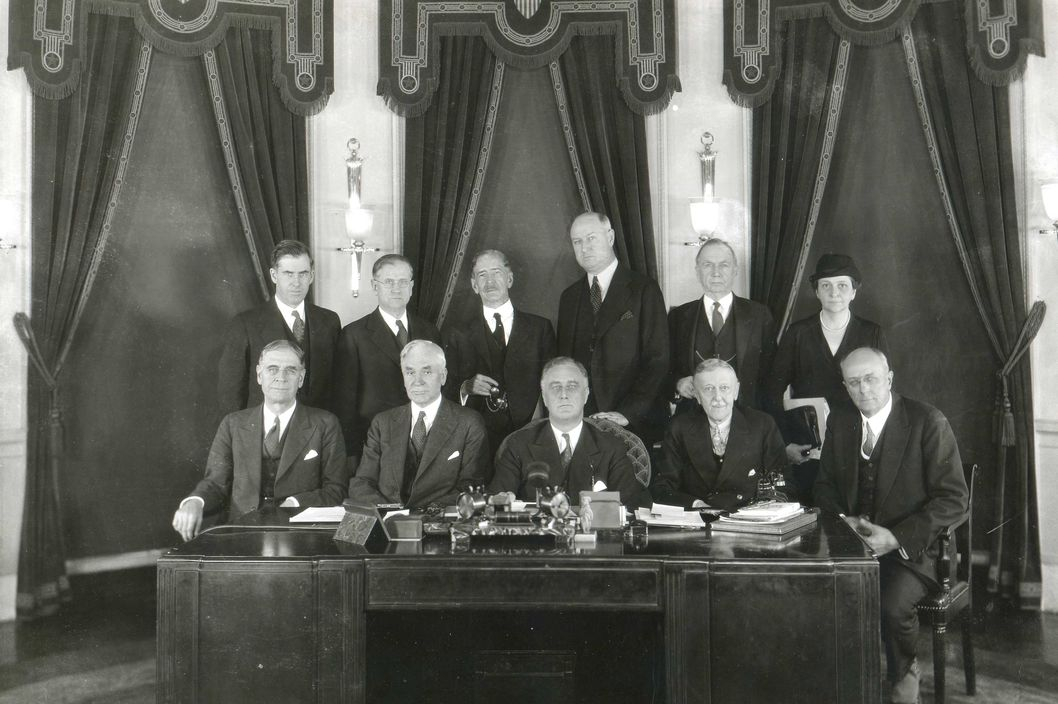 1933 - President Franklin D. Roosevelt (center) and his 1933 cabinet. Seated from left to right: Geroge H. Dern, Sec. of War; Cordell Hull, Sec of State; Roosevelt; W.H. Woodin, Sec of Treasury; Homer S. Cummings, Attorney General. Back Row left to right:  Henry A. Wallace, Sec. of Agriculture; Harold L. Ickes, Sec of Interior; C.A. Swanson, Sec of Navy; James A. Farley, Postmaster General; D.C. Roper, Sec. of Commerce; and Frances Perkins, Sec of Labor.
