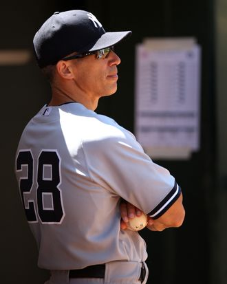 Manager Joe Girardi #28 of the New York Yankees watches from the dugout during the game against the Oakland Athletics